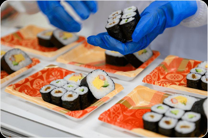スーパーのおにぎりや巻き寿司やお弁当などを炊飯工場でパッケージする様子